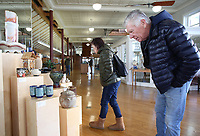 NWA Democrat-Gazette/DAVID GOTTSCHALK Kathy (left) and Chris Pare look Wednesday, January 9, 2019, at handcrafted pottery created by members of the Boston Mountain Potters Association at the Bank of Fayetteville on the square in Fayetteville. The pottery, all available for purchase, will be up through the month of January.