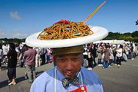 "A man advertising fried noodles. B1 Grand Prix, Yokote, Akita Pref, Japan, September 20 2009. The B1 Grand Prix is a competition for inexpensive and tasty regional dishes from around Japan. The B stands for ""b-class gourmet"". In 2009 it was held in the northern Japan city of Yokote."