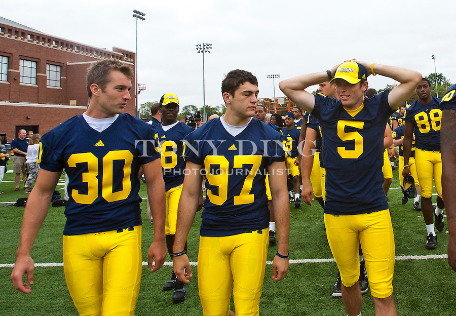 Michigan wide receiver Doug Rogan (30), kicker Scott Schrimscher (97), and quarterback Tate Forcier (5) walk with teammates at the annual NCAA college football media day, Sunday, Aug. 22, 2010, in Ann Arbor, Mich. (AP Photo/Tony Ding)