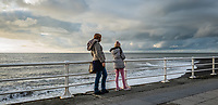 A woman and a young girl enjoy the view of the bay in Aberystwyth, Wales, UK. Sunday 03 November 2019