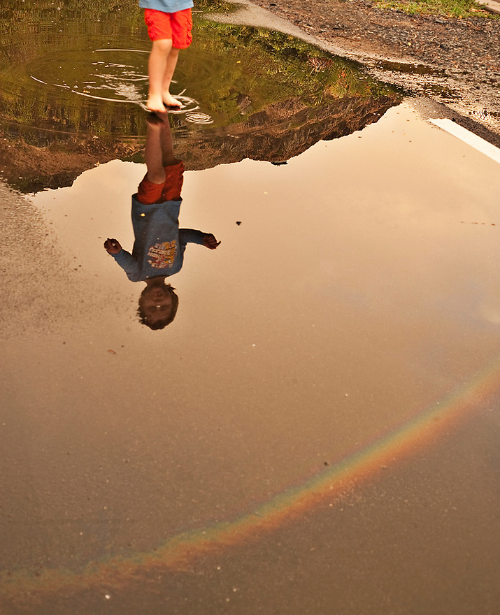 Child and rainbow reflection in rain puddle.  Liisa Roberts Photography