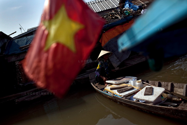 "A Vietnamese woman sells drinks to fishermen on the Hau Giang River, a tributary of the Mekong River, in Chau Doc, in the An Giang Province, Vietnam. When the Mekong River reaches Vietnam it splits into two smaller riveres. The ""Tien Giang"", which means ""upper river"" and the ""Hau Giang"", which means ""lower river"". Photo taken on Monday, December 7, 2009. Kevin German / Luceo Images"