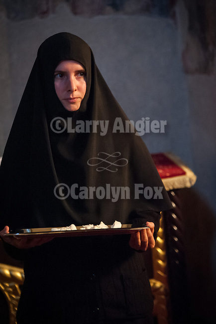 A nun holds a tray of bread during the Exultation of the Holy Cross service inside the Church of the Ascension of Jesus Christ at the Monastery Mileševa, Serbia originally built in the 13th century.