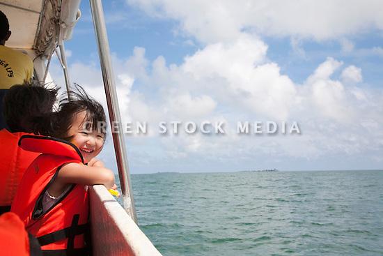 A happy girl (elementary age) enjoying a boat ride from Sandakan to Selingan Island (Turtle Island). Malaysia