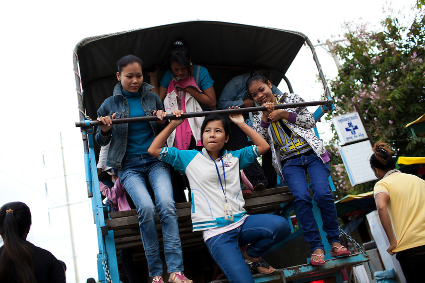 Garment workers climb down from a transport truck outside the Shen Zhou garment factory in Phnom Penh, Cambodia, Sept 14, 2011. For workers commuting from provinces outside Phnom Penh, transport costs are typically about US$10 per month.