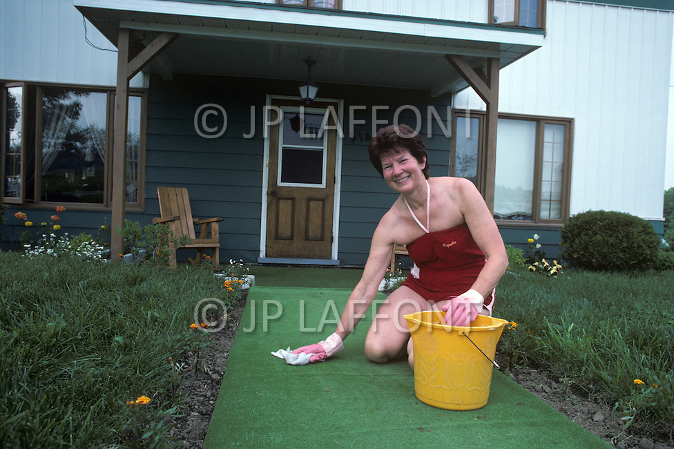 Ile D'Orleans, Quebec City Area, Canada, June 8, 1984. A citizen from the island cleaning the entrance of her house.