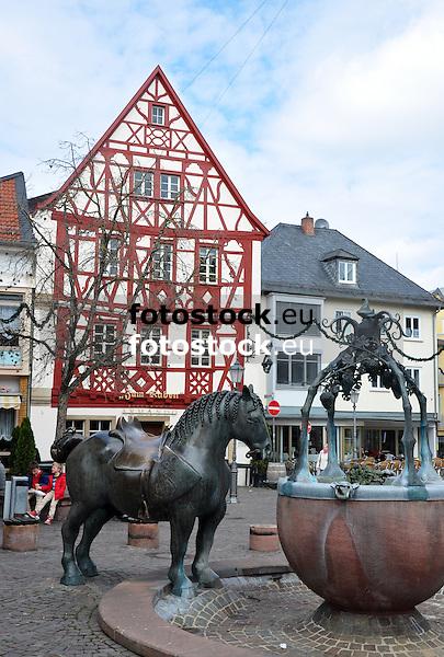 Rossmarktbrunnen (1985) des Neustadter Künstlers Prof. Gernot Rumpf auf dem Rossmarkt in Alzey, im Hintergrund ein typisches Fachwerkhaus