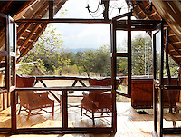 The terrace of a boutique style luxurious guesthouse  wooden treehouse. Made entirely of wood and grass, the tree-house, built 15ft above the ground, and offers a view of the Ngong Hills.