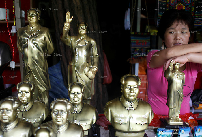 A stall owner stands next to Mao memorabilia on sale outside of  Mao's birthplace in Shaoshan, Hunan Province, China on 12 August 2009.  The village of Shaoshan, in rural Hunan Province, is tiny in size but big in name. It was the childhood home for Mao Zedong, the controversial revolutionary who came from obscurity but eventually defied all odds conquered China in the name of communism. Now his home, a sacred place among China's official propaganda, is in reality a microcosm of the country itself: part commercialism, part superstition, with a dash of communist ideological flavor.
