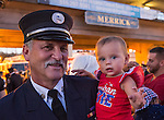 Merrick, New York, USA. 11th September 2015. RILEY E. GIES, one-year-old granddaughter of Fire Chief Ronnie E Gies who died responding to 9/11 NYC Terrorist Attack, is held by CRAIG MALTZ, a Bellmore volunteer firefighter, after Merrick Memorial Ceremony for Merrick volunteer firefighters and residents who died due to 9/11 terrorist attack at NYC Twin Towers. Ex-Chief Ronnie E. Gies of Merrick F.D. and FDNY Squad 288, and Ex-Captain Brian E. Sweeney, of Merrick F.D. and FDNY Rescue 1, died responding to the attacks on September 11, 2001.