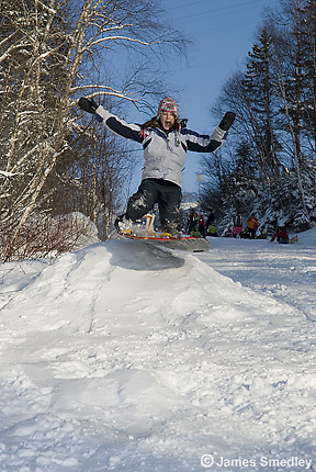 Kids sledding or toboganning down a hill in winter