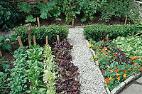 Small Vegetable garden with flowers & gravel stones pathway, wooden labels and rustic garden tool, edible flower nasturtiums Tropaeoleum, lettuce salad plants, watercress, tidy compact boxwood hedging buxus, stone edges, currants, tomatoes, chard