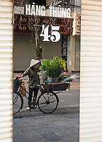 A Flower vendor in the Mirror an early morning street scene in Hanoi. Hanoi, the capital of Vietnam, is known for its centuries-old architecture and a rich culture with Southeast Asian, Chinese and French influences. At its heart is the chaotic Old Quarter, where the narrow streets are roughly arranged by trade. There are many little temples, including Bach Ma, honoring a legendary horse, plus Đồng Xuân Market, selling household goods and street food.