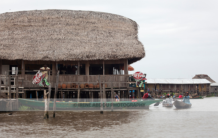 "Ganvie, Benin, with some 3,000 stilted buildings and a population of 20,000-30,000 people, may be the largest ""lake vllage"" in Africa.  In Ganvie, the population lives exclusively from fishing, building houses on stilts in and next to Lake Nokoue.  Because the Dan-Homey religion prohibited attacks on communities living in the water, the village of Ganvie dates back to the 16th or 17th century, when it was built to protect people from slavery.  Yet, even Ganvie hasn't escaped Coca Cola!!!"