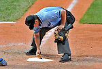 14 September 2008: Umpire Phil Cuzzi dusts off home plate during a game between the Cleveland Indians and the Kansas City Royals at Progressive Field in Cleveland, Ohio. The Royal defeated the Indians 13-3 to take the 4-game series three games to one...Mandatory Photo Credit: Ed Wolfstein Photo