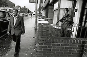 A man walks past a British soldier on foot patrol in the Falls Road, Belfast.