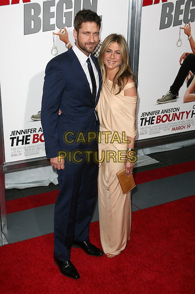 GERARD BUTLER & JENNIFER ANISTON.At the New York City film premiere of 'The Bounty Hunter' at Ziegfeld Theatre in New York City, NY, USA, .March 16, 2010 .arrivals  full length beard facial hair navy blue suit tie white shirt beige gold long maxi cut out off the shoulder dress nude clutch bag grecian bracelets .CAP/ADM/PZ.©Paul Zimmerman/Admedia/Capital Pictures