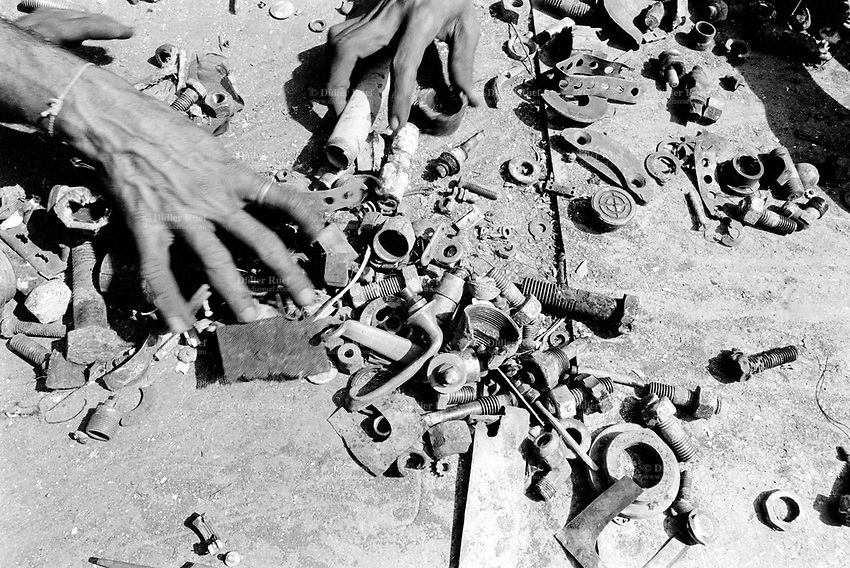 India. Province of Gujarat. Alang. Workers hands sort  out scrap's pieces. Alang, located in the Gulf of Khambhat, is a ships breaking place and is considered as the biggest scrapyard in the world. Ships recycling for its metals. Environmental issues. Hazardous waste. © 1992 Didier Ruef