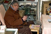 Un commerçant joue au solitaire dans son échoppe du marché aux oiseaux et aux fleurs en attendant le client..Shanghai, février 2006..