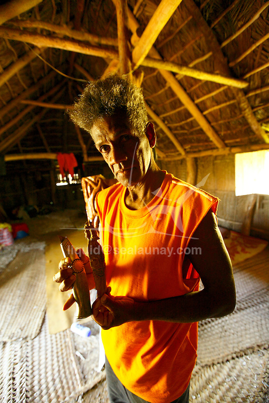 "Mister Ohmoou Waibo Felix  wood carver inside this house in the Fayaoue village on the Ouvea island in the Loyalty islands..Ouvéa (local pronunciation: [u?ve.a]) is a commune in the Loyalty Islands Province of New Caledonia, an overseas territory of France in the Pacific Ocean. The settlement of Fayaoué [fa?jawe], on Ouvéa Island, is the administrative centre of the commune of Ouvéa..Ouvéa is made up of Ouvéa Island, the smaller Mouli Island and Faiava Island, and several islets around these three islands. All these lie among the Loyalty Islands, to the northeast of New Caledonia's mainland..Ouvéa Island is one of the Loyalty Islands, in the archipelago of New Caledonia, an overseas territory of France in the Pacific Ocean. The island is part of the commune (municipality) of Ouvéa, in the Islands Province of New Caledonia..The crescent-shaped island, which belongs to a larger atoll, is 50 km (30 miles) long and 7 km (4.5 miles) wide. It lies northeast of Grande Terre, New Caledonia's mainland..Ouvéa is home to around 3,000 people that are organized into tribes divided into Polenesian, Melanesian and Walisian by ethnic descend. The Iaai language is spoken on the island..The two native languages of Ouvéa are the Melanesian Iaai and the Polynesian Faga Uvea, which is the only Polynesian language that has taken root in New Caledonia. Speakers of Faga Uvea have fully integrated into the Kanak society, and consider themselves Kanak..Ouvéa has rich marine resources and is home to many sea turtles, species of fish, coral as well as a native parrot, the Uvea Parakeet, that can only be found on the island of Ouvéa..A large crustacaen called a ""coconut crab"" or crabe de cocotier can also be found on the islands. The large crabs live in palm tree plantations and live solely on a diet of coconuts that they crack open with their powerful claws. They are blue in colour and can grow to several kilos in size. They are a land based species and do not venture into the ocean.."