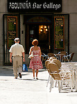 A couple walks past a bar in downtown Madrid, Spain. A woman in a red flowered dress, walks by a bar with her husband in downtown Madrid, Spain.