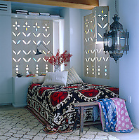 A Moroccan lantern hanging from a beam and a red and black suzani covering the bed give the bedroom an exotic feel