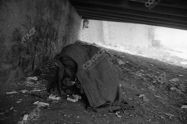 Drug addict under Kabul River bridge. Kabul, Afghanistan. March 2006