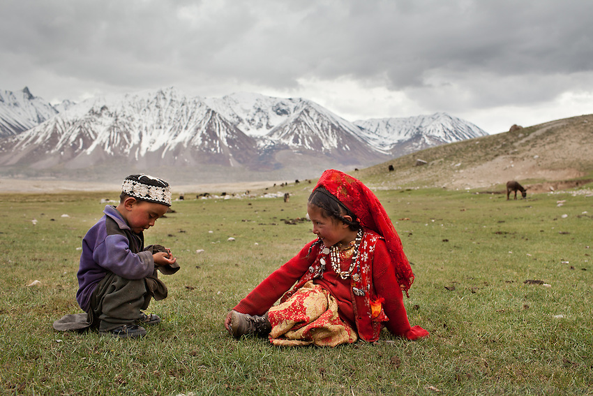 Two young Afghan Kyrgyz play in the grass in spring...The Kyrgyz settlement of Tchelab, near Chaqmaqtin lake, Haji Bootoo Boi's camp...Trekking through the high altitude plateau of the Little Pamir mountains (average 4200 meters) , where the Afghan Kyrgyz community live all year, on the borders of China, Tajikistan and Pakistan.