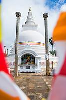 Sacred City of Anuradhapura, Thuparama Dagoba and the Buddhist flag, Sri Lanka, Asia. This is a photo of Thuparama Dagoba and the Buddhist flag in The Ancient City of Anuradhapura in the 'cultural triangle' area of Sri Lanka, Asia. Thuparama Dagoba is the oldest Dagoba in the Ancient City of Anuradhapura, and also Sri Lanka.