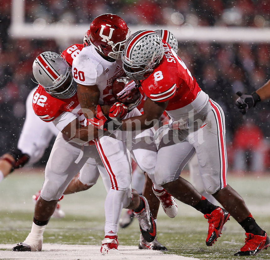 Indiana Hoosiers running back D'Angelo Roberts (20) is tackled by Ohio State Buckeyes defensive lineman Adolphus Washington (92) and Ohio State Buckeyes defensive lineman Noah Spence (8) during Saturday's NCAA Division I football game at Ohio Stadium in Columbus on November 23, 2013. Ohio State won the game 42-14. (Barbara J. Perenic/The Columbus Dispatch)
