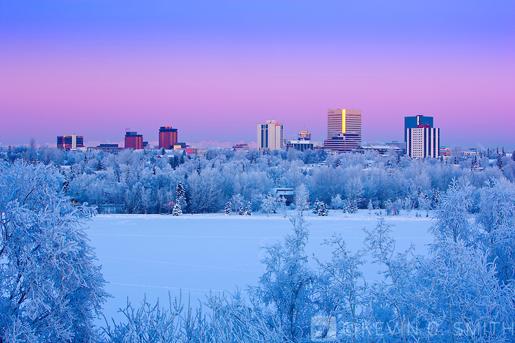 Alpenglow over the Anchorage skyline, winter, Southcentral Alaska, USA.