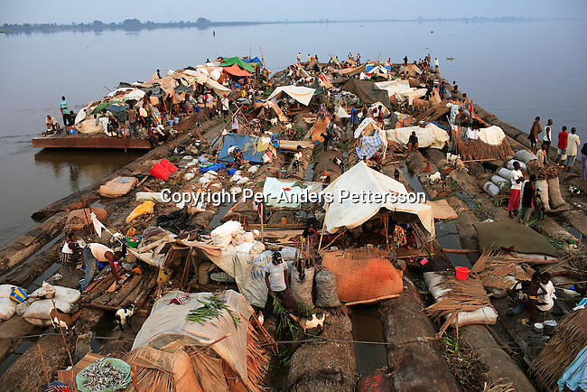 MBANDAKA, DEMOCRATIC REPUBLIC OF CONGO JUNE 29: Unidentified passengers travel on a boat made of big trees on the Congo River on June 29, 2006 outside Mbandaka, Congo, DRC. The boat traveled with about 150 passengers from Bumba to Kinshasa, a journey of about 1300 kilometers. The Congo River is a lifeline for millions of people, who depend on it for transport and trade. Passengers slept in the open, with their goats, pigs and other animals. Boat travel is the only option for most people along the river as there?s no roads or infrastructure. Very few can afford to fly in a plane to the capital Kinshasa. During the Mobuto era, big boats run by the state company ONATRA dominated the river. These boats had cabins and restaurants etc. All the boats are now private and are mainly barges that transport goods. The crews sell tickets to passengers who travel in very bad conditions. The conditions on the boats often resemble conditions in a refugee camp. Congo is planning to hold general elections by July 2006, the first democratic elections in forty years. The Congolese and the international community are hoping that Congo will finally have piece and the country will be rebuilt..(Photo by Per-Anders Pettersson/Getty Images)..