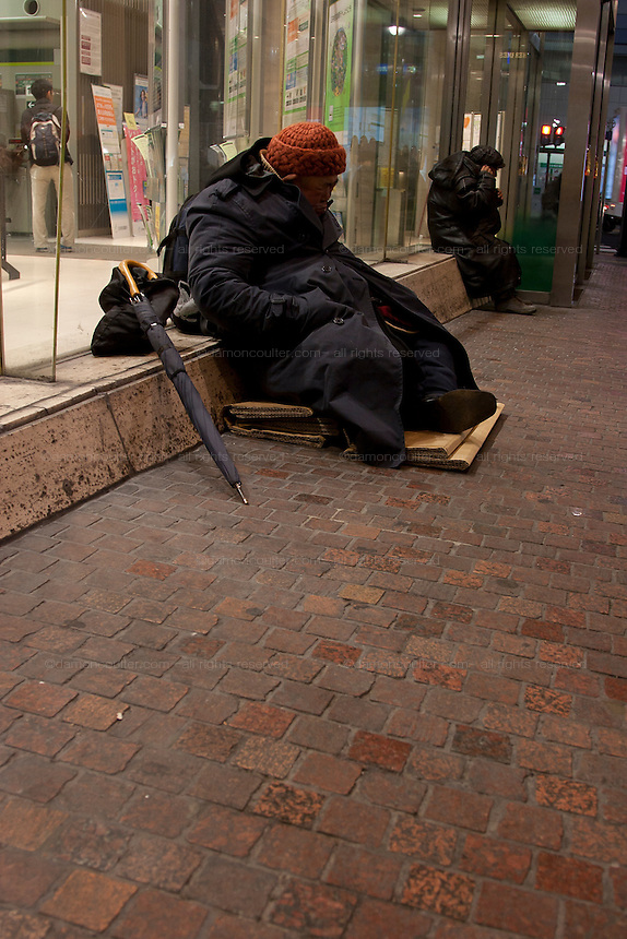 A homeless man sits by a department store window in Shibuya, Tokyo, Japan Thursday December 18th 2008