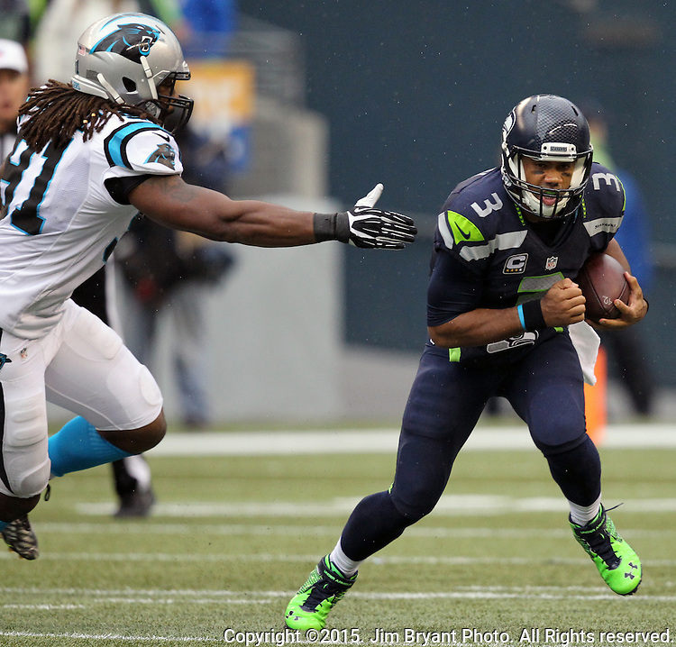Seattle Seahawks  Russell Wilson scrambles away from Carolina Panthers defensive end Ryan Delaire  (91) at CenturyLink Field in Seattle on October 18, 2015. The Panthers came from behind with 32 seconds remaining in the 4th Quarter to beat the Seahawks 27-23.  ©2015 Jim Bryant Photography. All Rights Reserved.