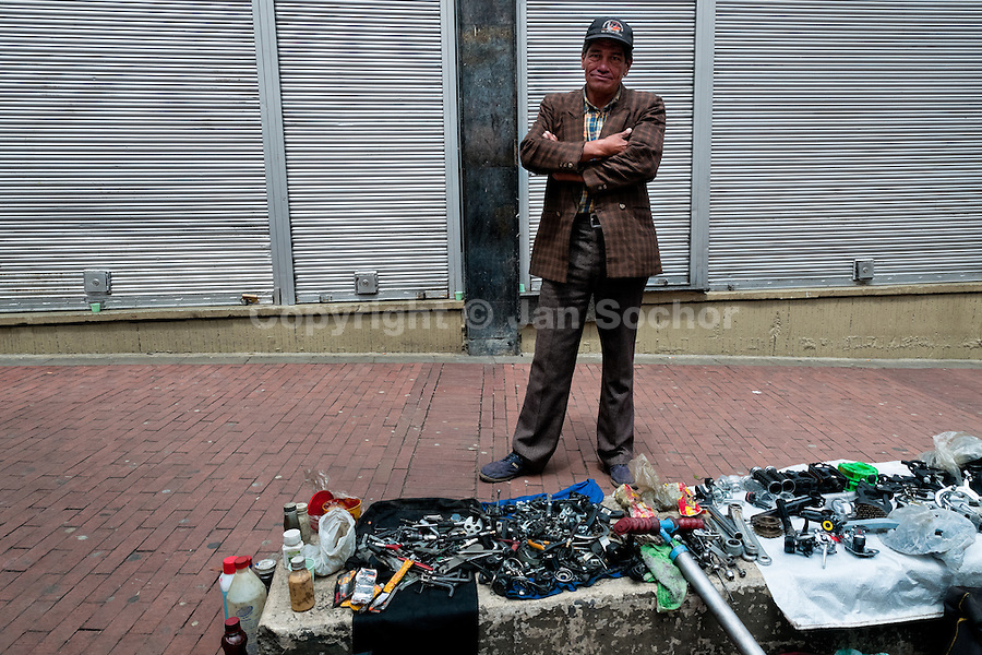 A Colombian service man stands in an improvised bicycle repair shop on the street during the Car Free Day in Bogota, Colombia, 23 May 2010.