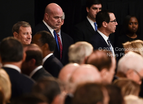 Member of the Supreme Court Chief Justice, John Roberts (L), acting Attorney General, Matthew Whitaker (C), and   Secretary of the Treasury, Steven Mnuchin (L) wait for the casket containing the remains of former US President George H.W. Bush to arrive at the US Capitol during a State Funeral in Washington, DC, December 3, 2018. - The body of the late former President George H.W. Bush will travel from Houston to Washington, where he will lie in state at the US Capitol through Wednesday morning. Bush, who died on November 30, will return to Houston for his funeral on Thursday. (Photo by Brendan SMIALOWSKI / AFP)