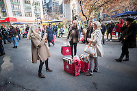Shoppers in Herald Square outside Macy's Herald Square flagship store in New York looking for bargains on Black Friday, the day after Thanksgiving, Friday, November 29, 2013. Many retailers, including Macy's, opened their doors on Thanksgiving or opened up for Black Friday the night before extending the shopping day into over 24 hours. (© Richard B. Levine)