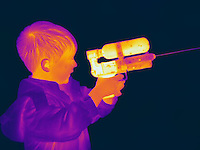 A Thermogram of a boy with a squirt gun.  The different colors represent different temperatures on the object. The lightest colors are the hottest temperatures, while the darker colors represent a cooler temperature.  Thermography uses special cameras that can detect light in the far-infrared range of the electromagnetic spectrum (900?14,000 nanometers or 0.9?14 µm) and creates an  image of the objects temperature..