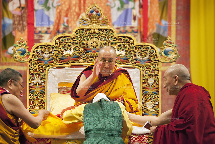 """Switzerland. Basel. St. Jakobshalle. His Holiness the Dalai Lama is blessing a woman before his public lecture on Bodhicitta. The topic of his talk is about Nagarjuna's Commentary on Bodhicitta which touches on two aspects of the awakening mind, the twin qualities of wisdom and compassion, which are necessary for anyone who aspires to be a better person and implement changes in their lives. The 14th and current Dalai Lama is Tenzin Gyatso, recognized since 1950. He is the current Dalai Lama, as well as the longest-lived incumbent, well known for his lifelong advocacy for Tibetans inside and outside Tibet. Dalai Lamas are amongst the head monks of the Gelug school, the newest of the schools of Tibetan Buddhism. The Dalai Lama, also called """" Ocean of Wisdom"""" is considered as the incarnation of Chenresi, the Bodhisattva of compassion who is also the protective deity of Tibet. 7.02.2015 © 2015 Didier Ruef"""