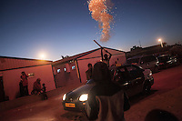 November 13, 2014 - Tripoli City, Libya: Tawerghans youth burn fireworks as they celebrate a wedding in a construction site in the Fallah road of Tripoli used as a temporary shelter after the Tawerghans were forced to move from their city home in southeast of Misrata as they were harassed by the armed militias of Misrata during the 2011 uprising against Colonel Gaddafi. (Photo/Narciso Contreras)