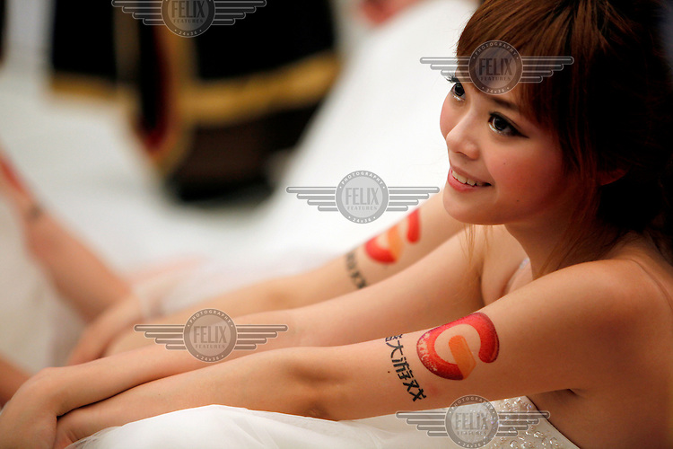 A model, sporting a transfer logo of Shanda Games Limited,  on her arm takes a break between shows at the ChinaJoy Expo, also know as the China Digital Entertainment Expo and Conference.