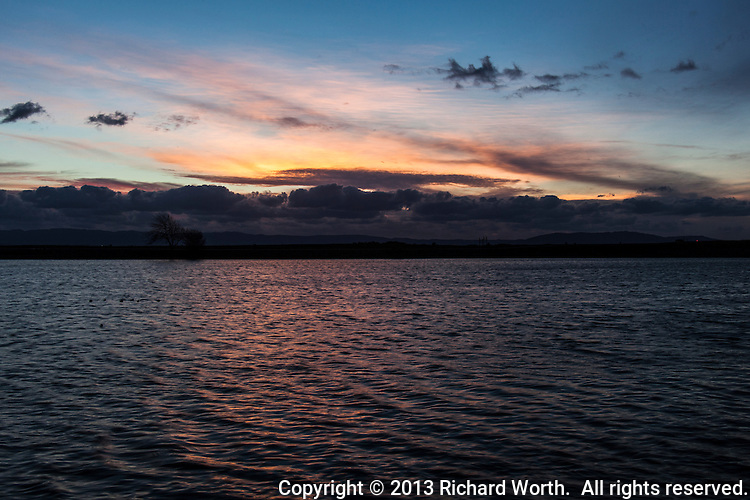 Sunset's orange and gold  slide past the clouds and land to dance on the rippled waters of San Francisco Bay at San Leandro Marina Park,