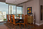 View of a contemporary Dining Room in a Richmond VA condo, Vistas on the James. Colorful artwork and glass sculpture, a modern dining room table and chairs with a view of downtown Richmond.