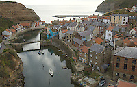 The picturesque fishing village of Staithes, North Yorkshire, England, where the great explorer Captain James Cook was once apprenticed to a draper, clings to the steep cliffs round its tight little harbour and narrow inlet.