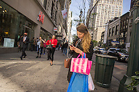 A woman texts on her smartphone with her Victoria's Secret purchase in Herald Square in New York on Thursday, April 30, 2015. (© Richard B. Levine)