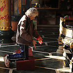 Bao-jhong Yi-min Temple, Kaohsiung -- A Taoist worshiper praying.<br /> <br /> This elder lady throws two half-moon shaped, wooden oracle chips called 'zhi jiao' to the ground.<br /> <br /> The 'zhi jiao' are used to communicate with a god. The worshiper asks the god a simple yes/no questions, and then throws the two pieces own the floor in front of him. There are three possibilities how the pieces end up: both are facing down, both are facing up, or one each faces up and down.<br /> <br /> If one piece lands face up and the other one face down, the god's answer to the question posed is affirmative. If both pieces come to lie face down the answer is 'no'.<br /> Should both pieces lie face up the god simply gives a smile. This means that he refuses to answer the question, in which case the Taoist believer proceeds to ask a similar, but slightly question until he gets an answer from the god.