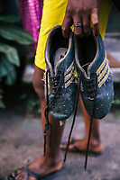 JAIPALGURI, INDIA- AUGUST 16: Player and coach of the female football team, the Dooars XI,  Bhabani Munda, 24, walks with her football shoes prior to the start of a training session on August 16, 2013 at the Kalchini tea estate In Jalpaiguri district , West Bengal, India. The Kalchini tea estate where Bhabani Munda lives is one of the most interior and backwards regions in north Bengal. The tea estates of North Bengal, including the Kalchini tea estate, were in news in 2007-08 for large-scale starvation deaths owing to malnutrition. Even today one person dies every day due to starvation in the north Bengal tea estates. In the last decade there have been 3500 deaths in these tea estates. (Photo by Daniel Berehulak for Time Magazine)