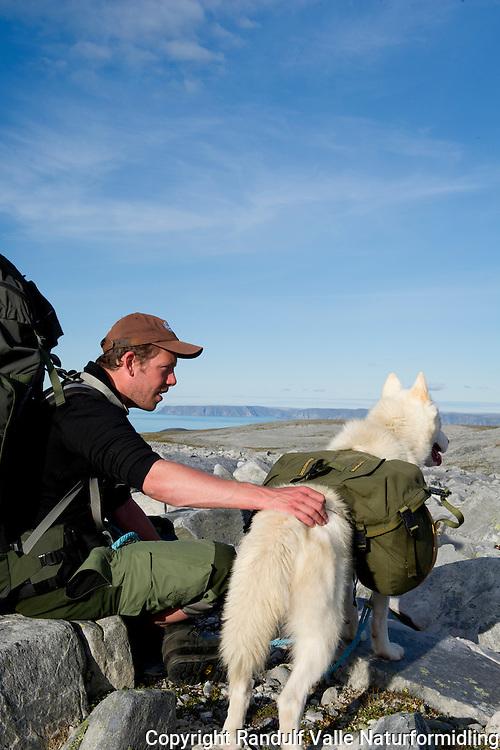 Mann og grønlandshund i høyfjellsterreng på Sværholthalvøya. Norkynn i bakgrunnen. ---- Man and greenland dog on Sværholt peninsula.