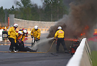 Mar 18, 2016; Gainesville, FL, USA; NHRA safety safari rescue crews pull pro mod driver Dan Stevenson from his burning car after an engine explosion and fire during qualifying for the Gatornationals at Auto Plus Raceway at Gainesville. Mandatory Credit: Mark J. Rebilas-USA TODAY Sports