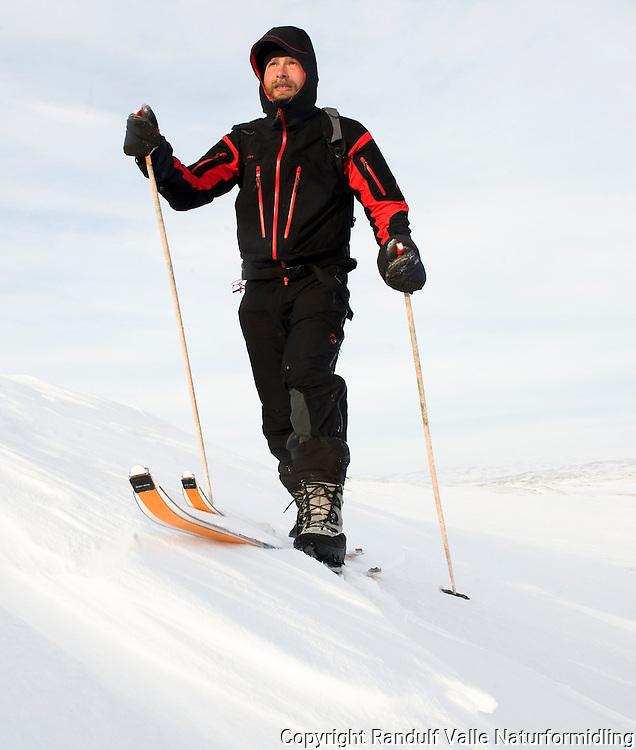 Mann går på ski med skifeller. ---- Man skiing.